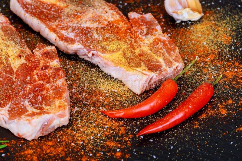 Filete de carne de vaca crudo con las especias y los ingredientes para cocinar en borard del corte imagenes de archivo