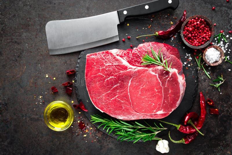 Filete de carne de vaca crudo en fondo negro con cocinar los ingredientes Carne fresca de la carne de vaca fotografía de archivo