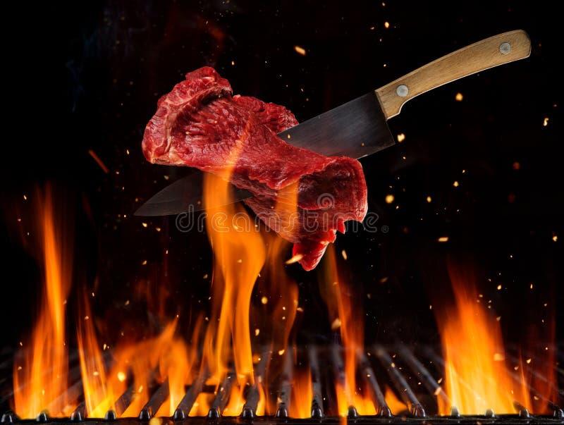 Filete de carne de vaca crudo que vuela sobre rejilla ardiendo de la parrilla libre illustration