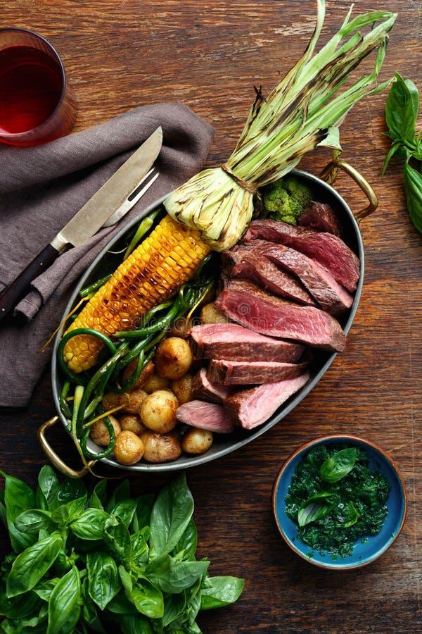 Filete de carne de vaca de las rebanadas en sartén con las verduras y el vino rojo imagenes de archivo