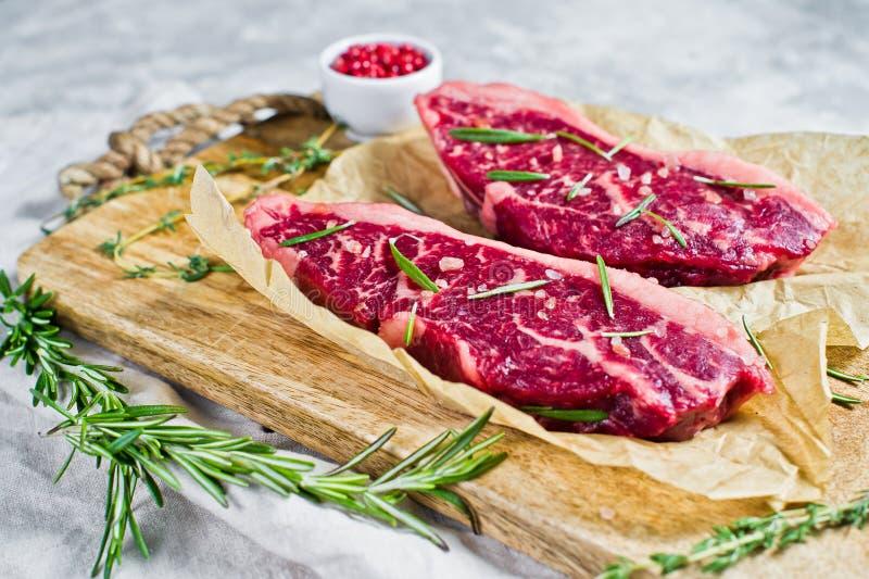 Filete de carne de vaca veteado crudo Angus negro en una tajadera de madera con romero y pimienta rosada Fondo gris, visi?n super imagen de archivo