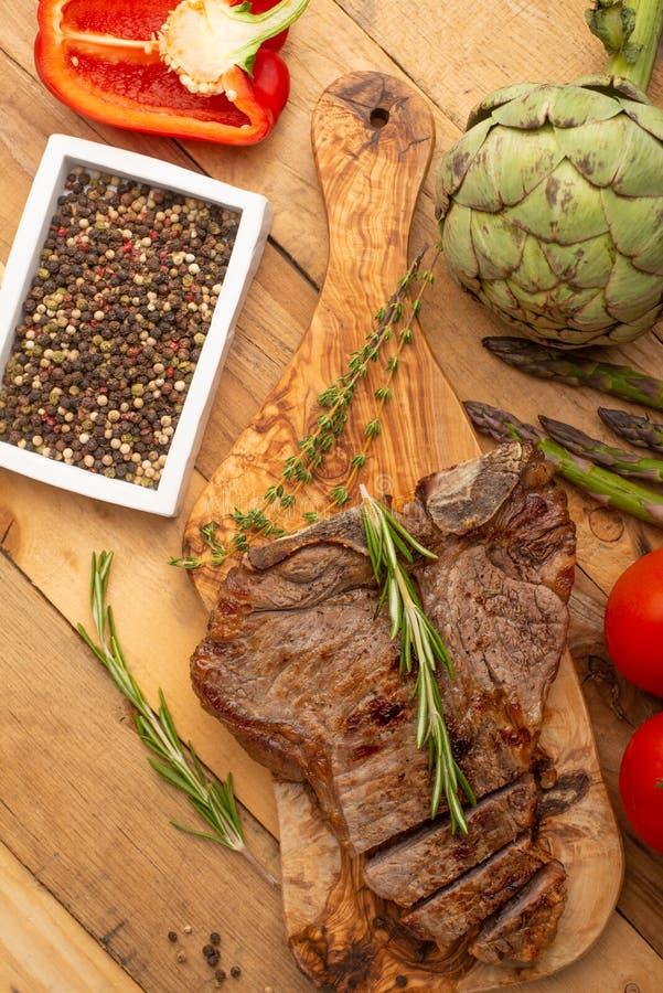 Filete de carne de vaca veteado en un tablero con pimienta del romero, condimento, y verduras frescas, tomates y espárrago, alcac imágenes de archivo libres de regalías