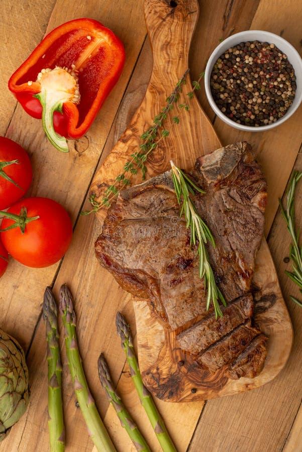 Filete de carne de vaca veteado en un tablero con pimienta del romero, condimento, y verduras frescas, tomates y espárrago, alcac imagen de archivo libre de regalías