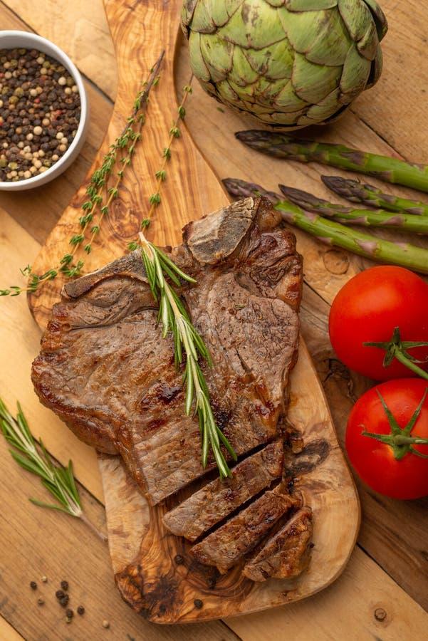 Filete de carne de vaca veteado en un tablero con pimienta del romero, el condimento, y verduras frescas en un fondo de madera, m fotos de archivo libres de regalías