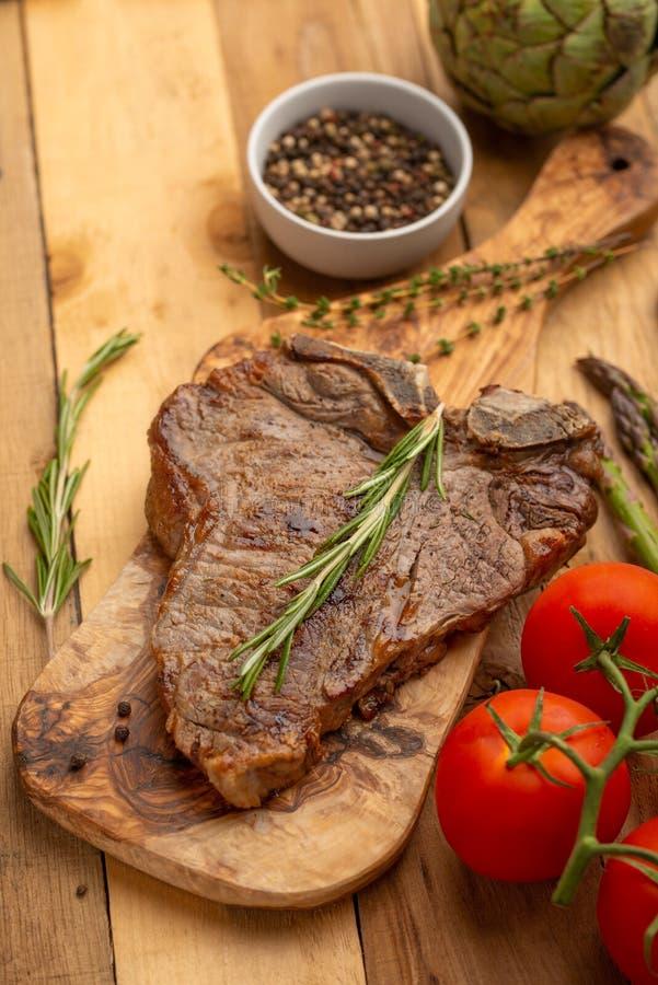 Filete de carne de vaca veteado en un tablero con pimienta del romero, el condimento, y verduras frescas en un fondo de madera, m fotografía de archivo libre de regalías