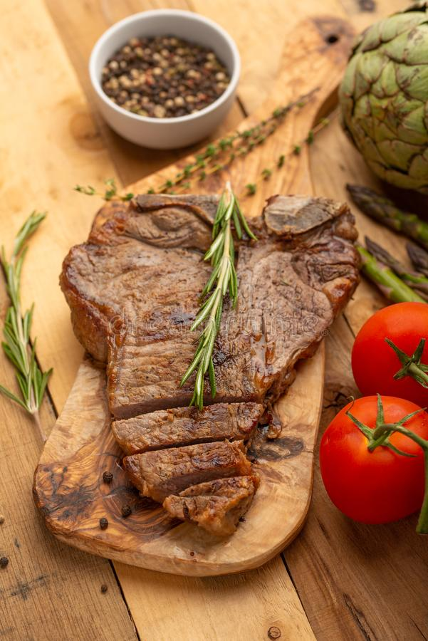 Filete de carne de vaca veteado en un tablero con pimienta del romero, el condimento, y verduras frescas en un fondo de madera, m imagen de archivo
