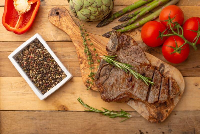 Filete de carne de vaca veteado en un tablero con pimienta del romero, el condimento, y verduras frescas en un fondo de madera, m fotografía de archivo