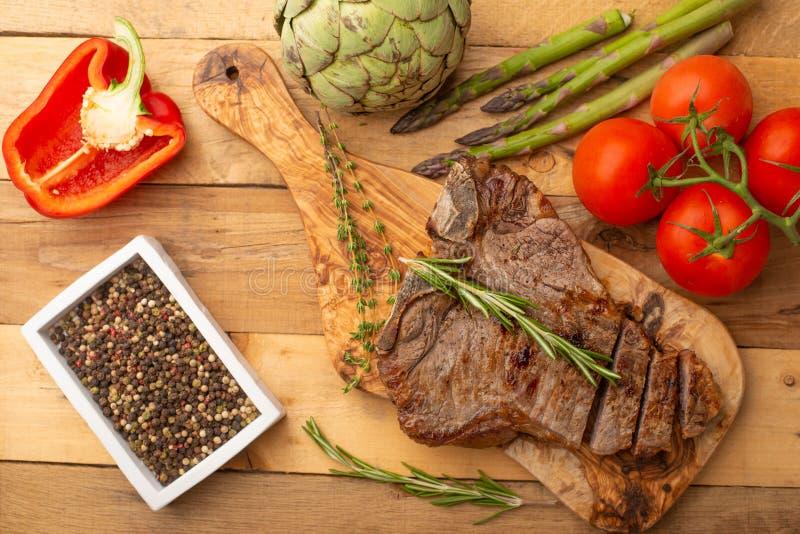 Filete de carne de vaca veteado en un tablero con pimienta del romero, el condimento, y verduras frescas en un fondo de madera, m foto de archivo libre de regalías