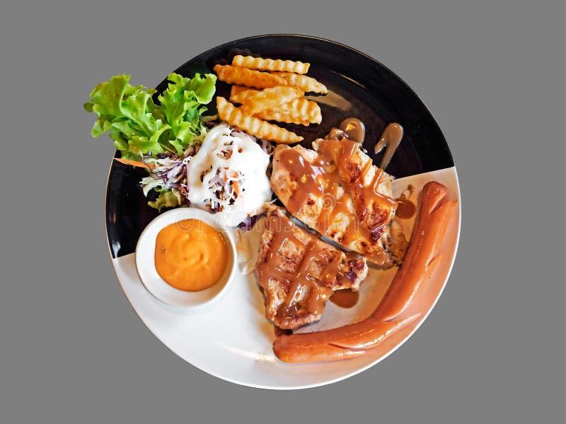 Filete de chuleta de cerdo con el pollo asado a la parrilla, salchicha, patatas fritas y foto de archivo libre de regalías