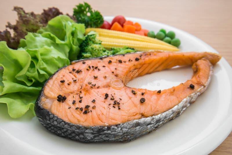 Filete de color salmón asado a la parrilla con las verduras en la placa imagen de archivo libre de regalías