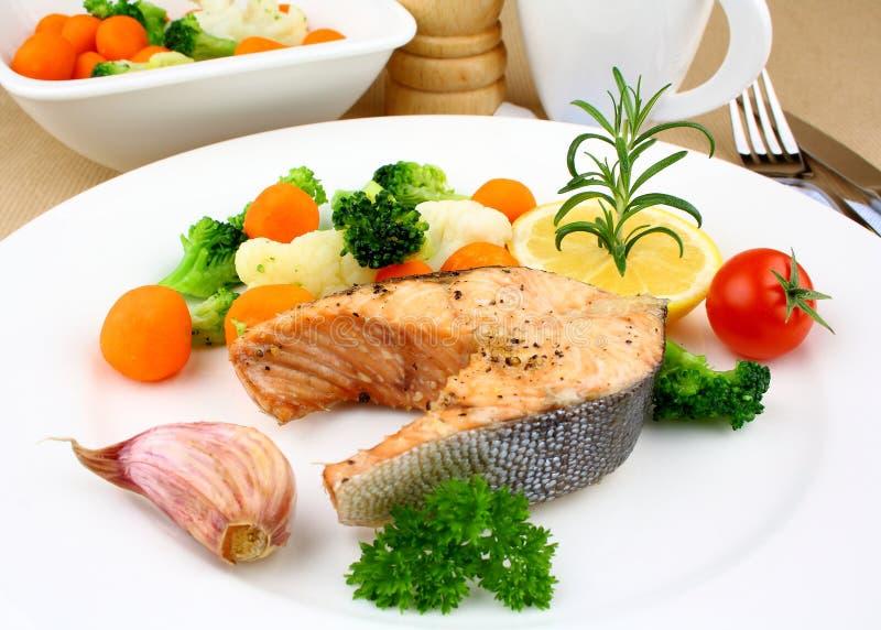 Filete de color salmón asado a la parrilla con las verduras en la placa blanca fotografía de archivo libre de regalías