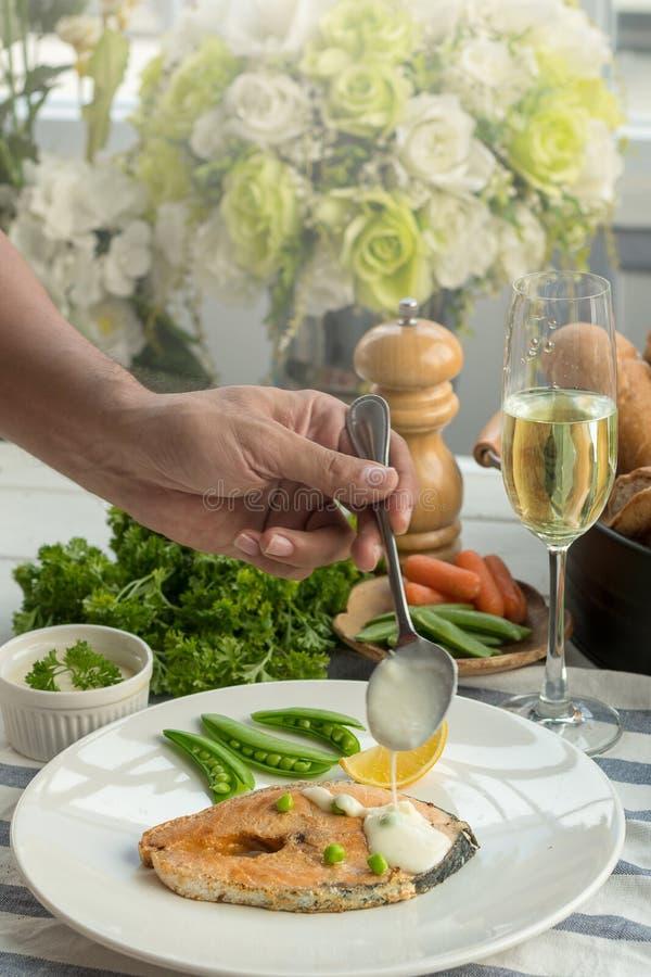 Filete de color salmón asado a la parrilla con las verduras y la salsa blanca imagenes de archivo