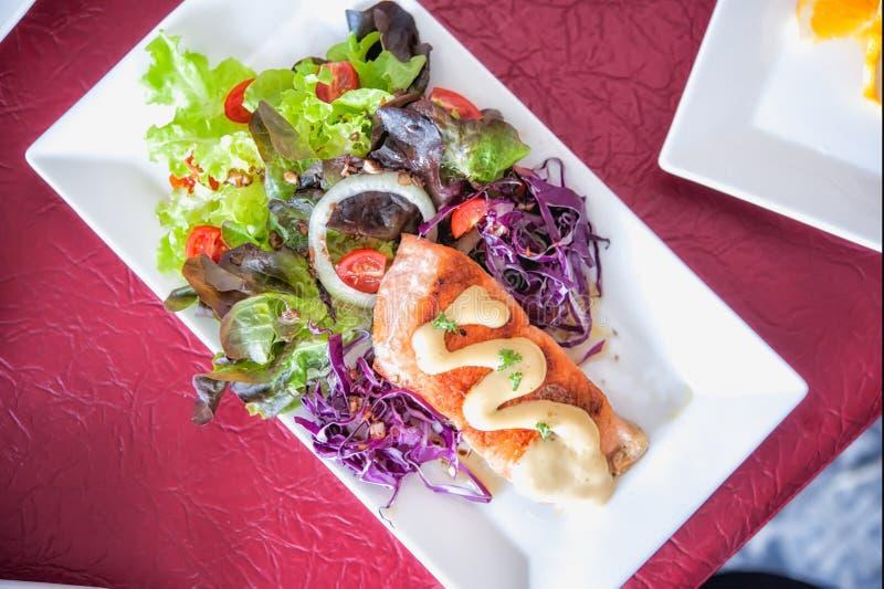 Filete de color salmón asado a la parrilla curruscante con la ensalada fotos de archivo