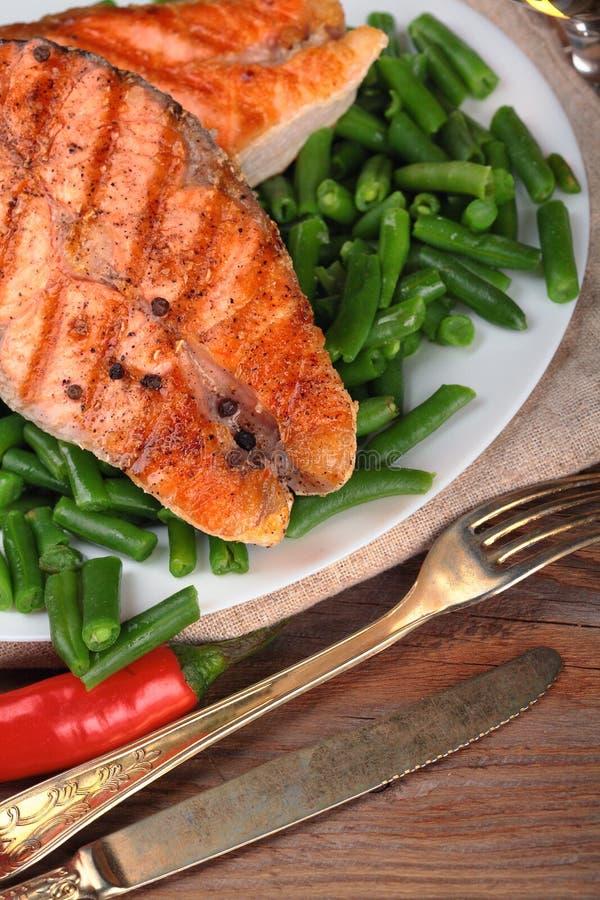 Filete de color salmón asado a la parrilla en habas de las cebolletas Sal del mar En el vector de madera Pimienta de chiles prime imagen de archivo libre de regalías