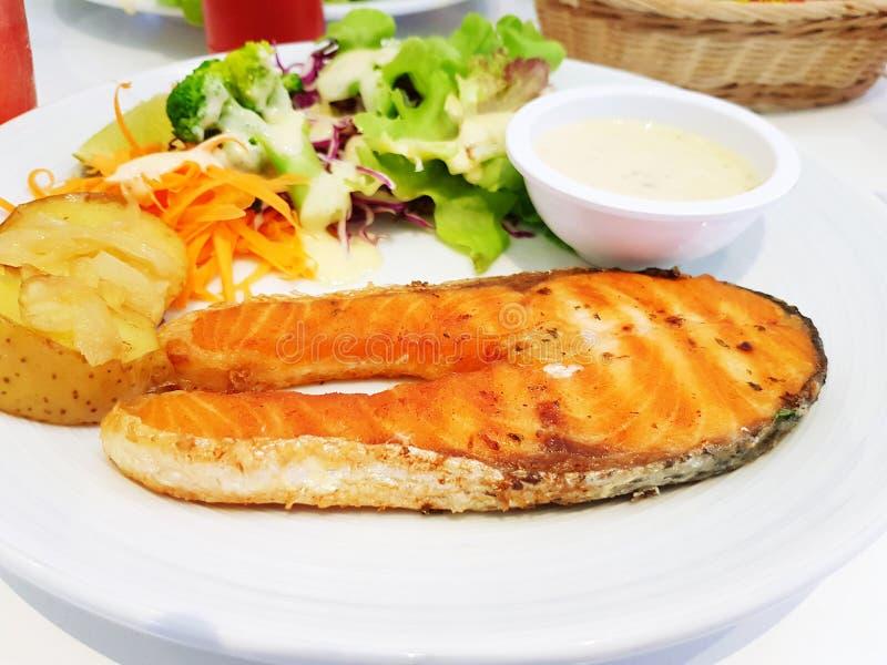 Filete de color salmón asado a la parrilla, patata hervida y ensalada con la salsa cremosa blanca en la placa blanca fotos de archivo libres de regalías
