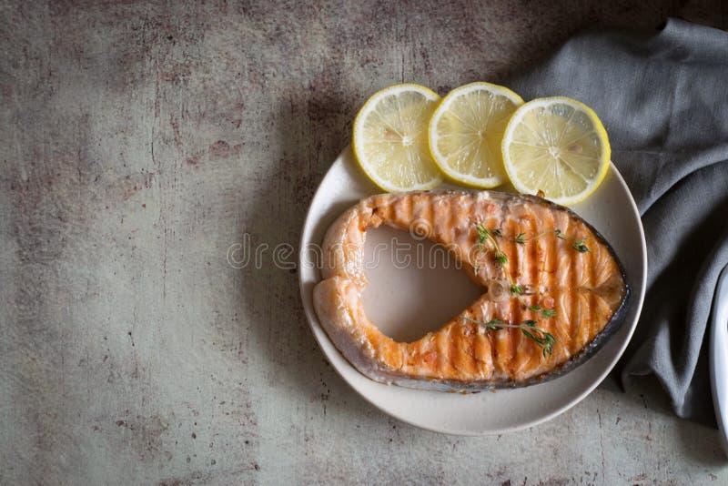 Filete de color salmón bien hecho en una placa de limones fotografía de archivo