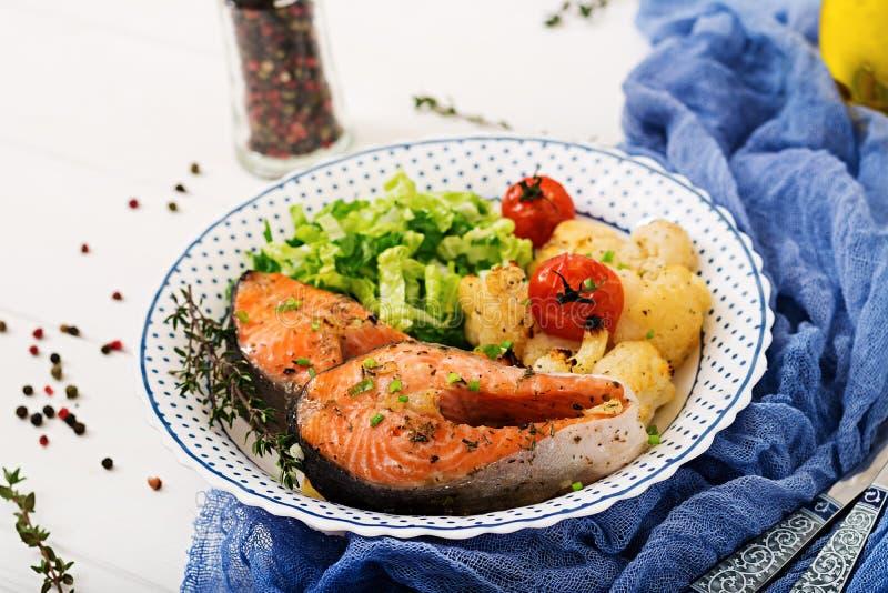 Filete de color salmón cocido con la coliflor, los tomates y las hierbas fotos de archivo