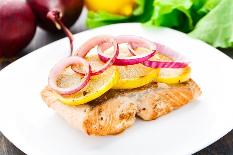 Filete de color salmón con el limón y la cebolla fotos de archivo