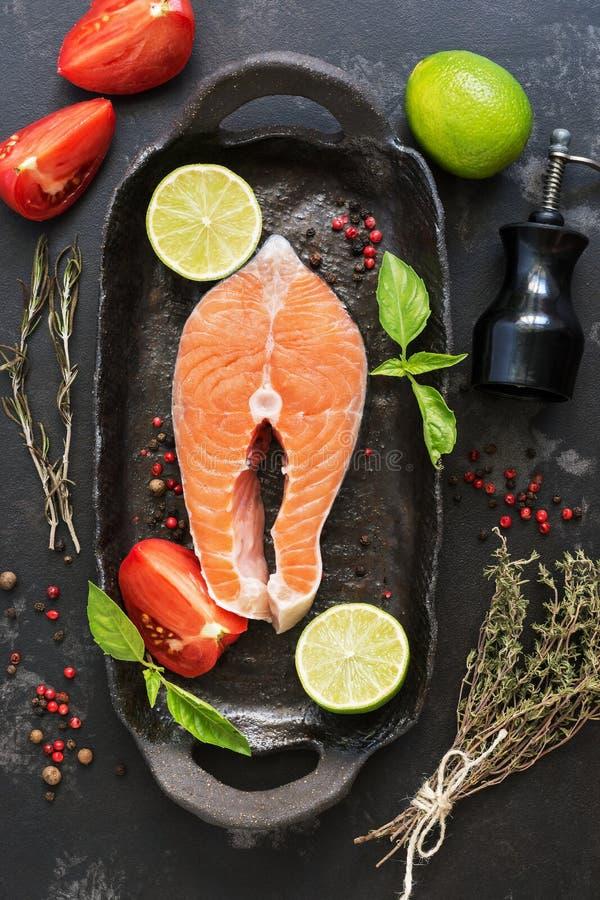 Filete de color salmón crudo con las especias y las hierbas en un sartén rústico, fondo de piedra negro Visión superior, endecha  imágenes de archivo libres de regalías