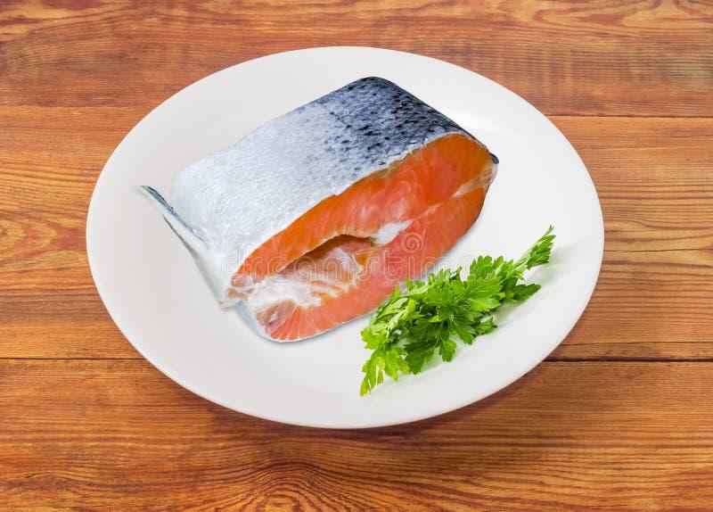 Filete de color salmón crudo con perejil en un plato blanco imagenes de archivo