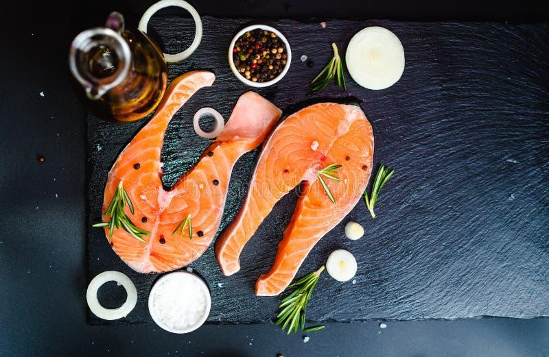 filete de color salmón, pimienta y sal, hierbas en la tabla concreta de piedra negra, opinión superior del espacio de la copia fotografía de archivo libre de regalías