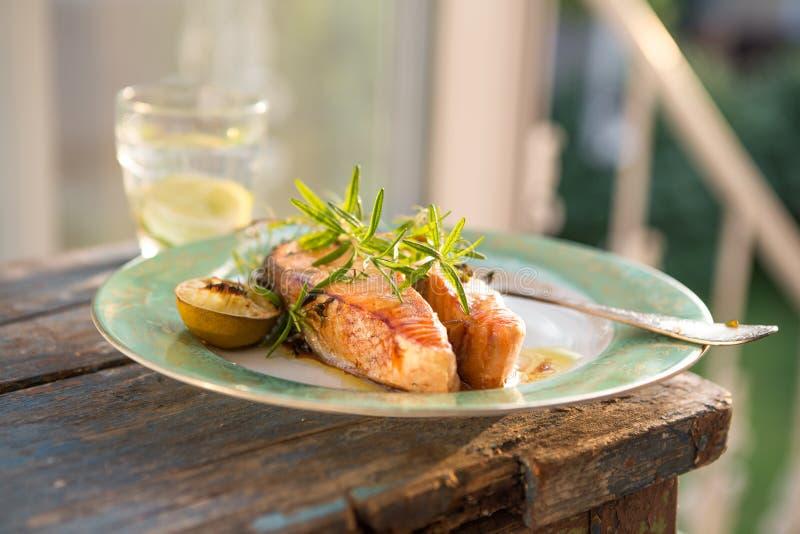 Filete de color salmón rojo asado a la parrilla servido con el limón y la lechuga en la placa blanca Salmones de Sockeye, salmone imagen de archivo libre de regalías