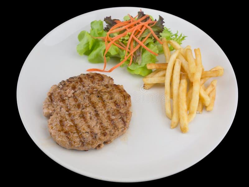 Filete de hamburguesas con las patatas fritas, el pan y la verdura aislados imagen de archivo libre de regalías