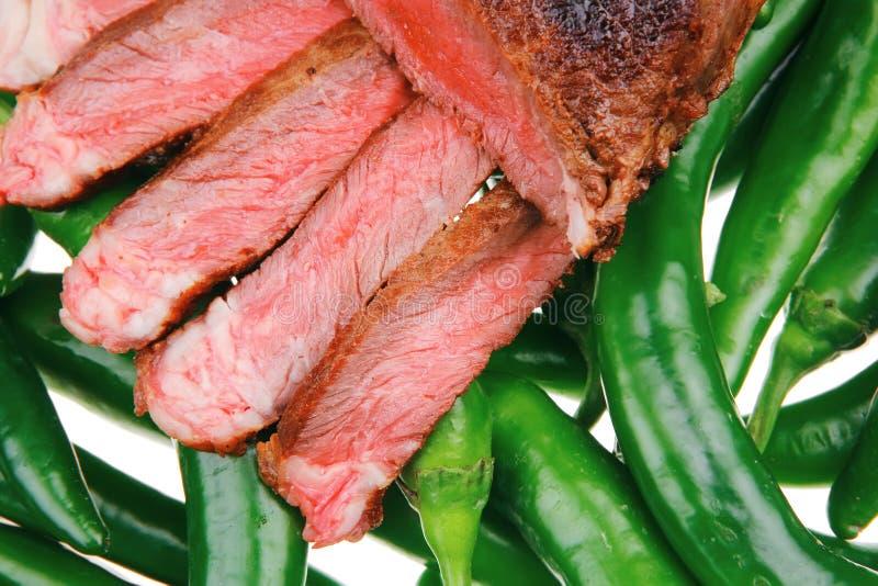 Filete de la carne cortado sobre las pimientas verdes del chile picante fotos de archivo
