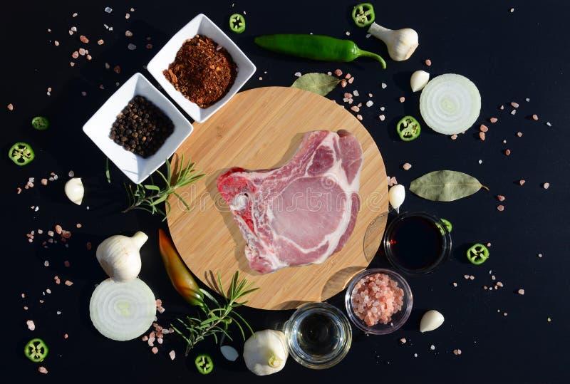 Filete de la carne en una tabla de cortar y una pimienta, hoja de laurel, romero, cebollas, sal, aceite de oliva, salsa de soja fotos de archivo libres de regalías