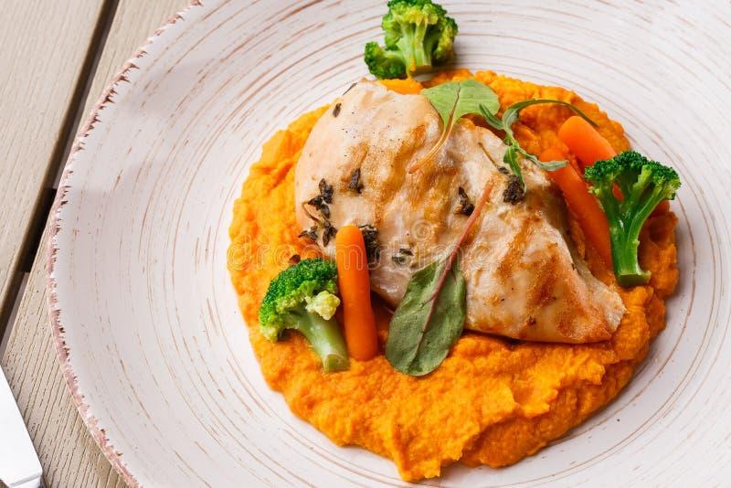 Filete de la pechuga de pollo con la zanahoria y el bróculi de bebé del puré de la zanahoria Rebanada asada a la parrilla del pol imágenes de archivo libres de regalías