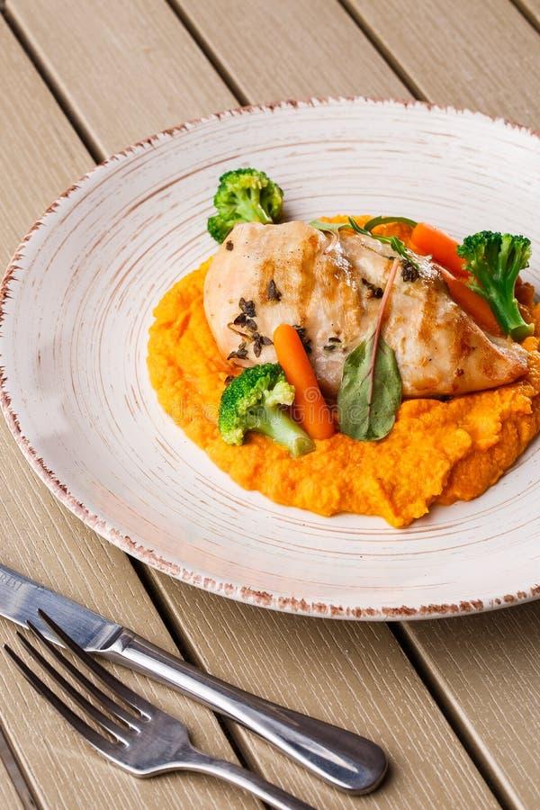 Filete de la pechuga de pollo con la zanahoria y el bróculi de bebé del puré de la zanahoria Rebanada asada a la parrilla del pol fotos de archivo