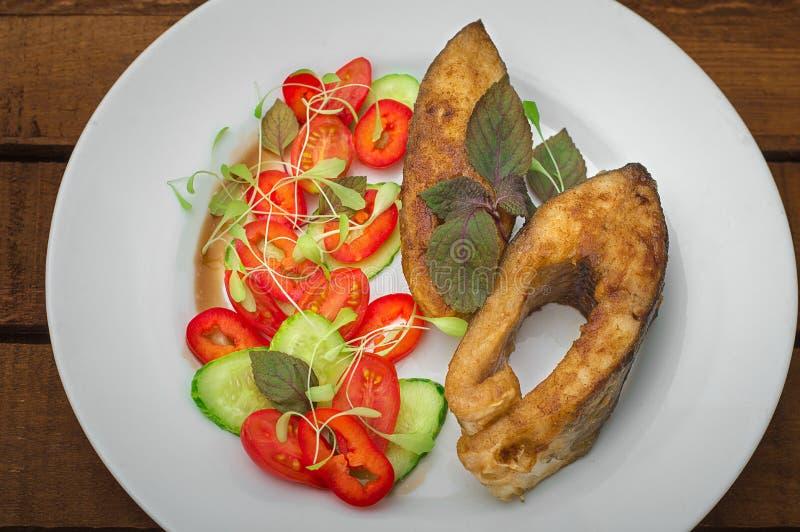 Filete de pescados asado a la parrilla con las verduras en la placa: cena de los tomates, del microgran, del pepino, sabrosa y sa imagen de archivo