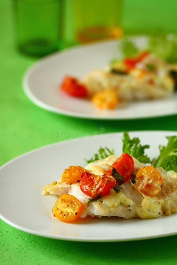 Filete de pescados cocido al horno con el tomate foto de archivo
