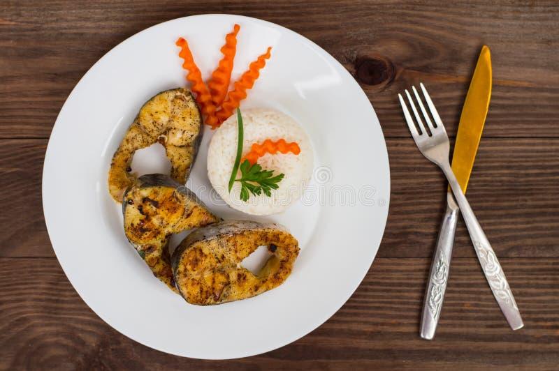 Filete de pescados frito con arroz y zanahorias hervidos Visión superior Primer fotos de archivo libres de regalías