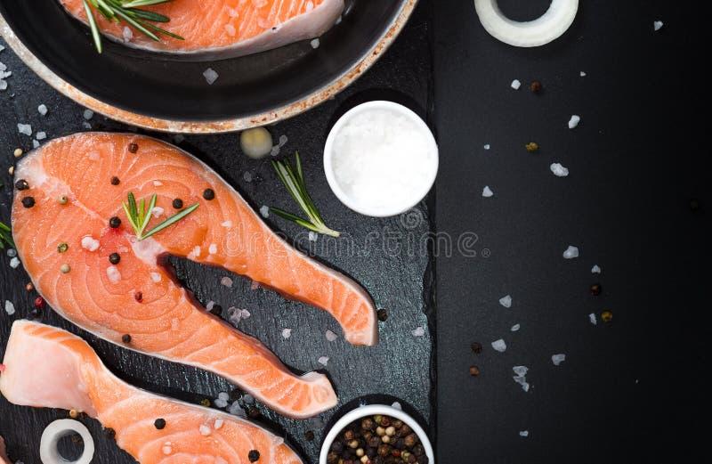filete de salmón crudo sobre fondo de piedra oscura con cebollas, romero, especias, dieta conceptual, grasas insaturadas, omega 3 imagen de archivo libre de regalías