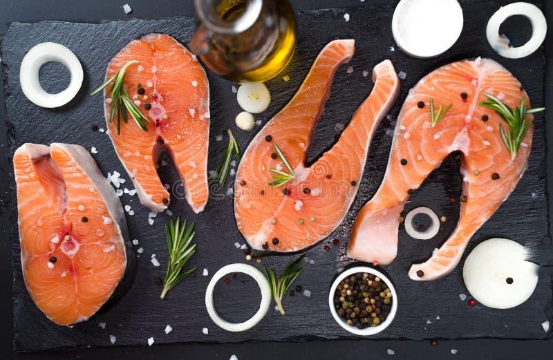 filete de salmón crudo sobre fondo de piedra oscura con cebollas, romero, especias, dieta conceptual, grasas insaturadas, omega 3 imagen de archivo