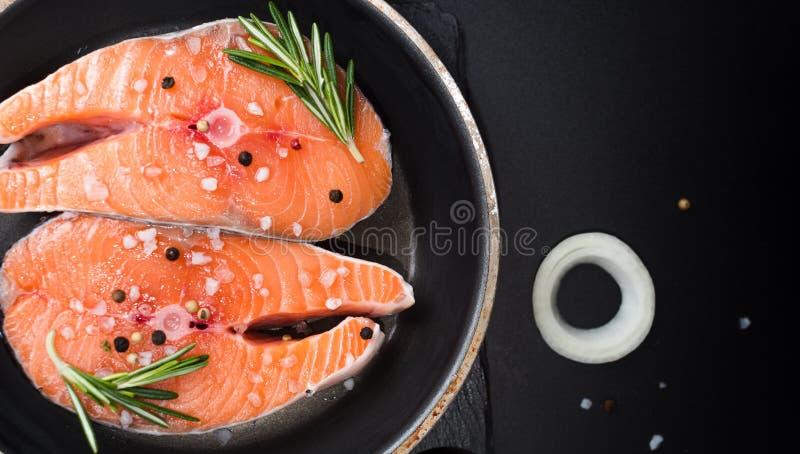filete de salmón crudo sobre fondo de piedra oscura con cebollas, romero, especias, dieta conceptual, grasas insaturadas, omega 3 imagenes de archivo