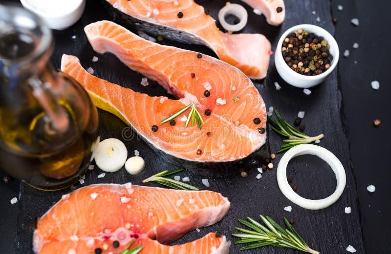 filete de salmón crudo sobre fondo de piedra oscura con cebollas, romero, especias, dieta conceptual, grasas insaturadas, omega 3 fotografía de archivo libre de regalías