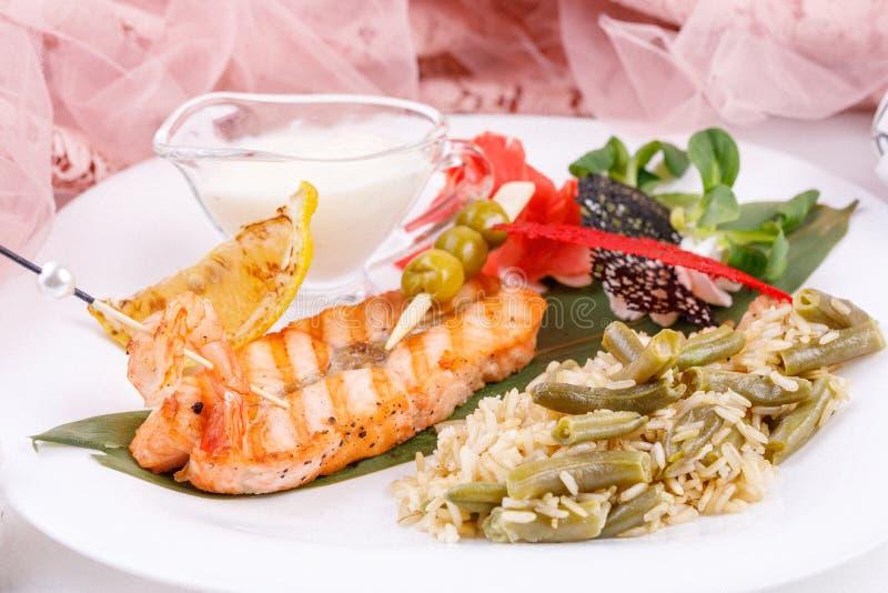 Filete de salmones con un acompañamiento del arroz y de las habas verdes fotografía de archivo libre de regalías