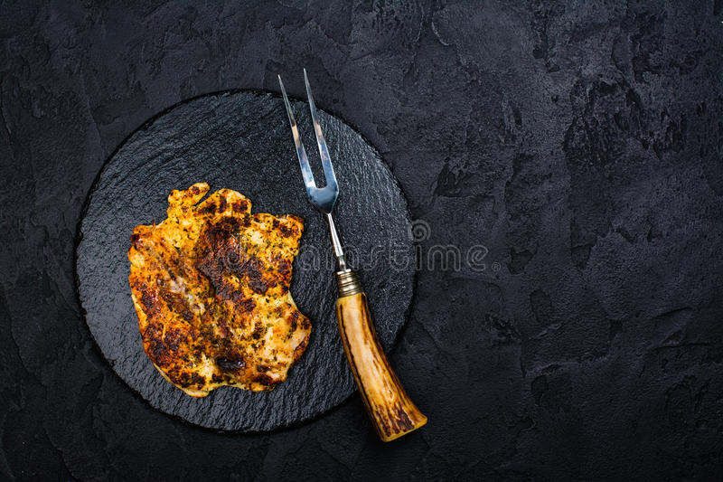 Filete del pollo en tablero de la pizarra imagen de archivo