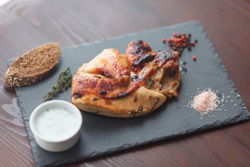 Filete del pollo frito con el souce y especia en tablero negro de la pizarra Foco selectivo imágenes de archivo libres de regalías