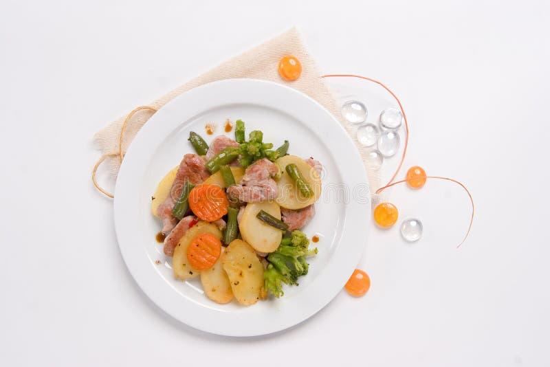 Filete hecho en casa de la rebanada con el bróculi y la zanahoria hervidos, patata asada foto de archivo