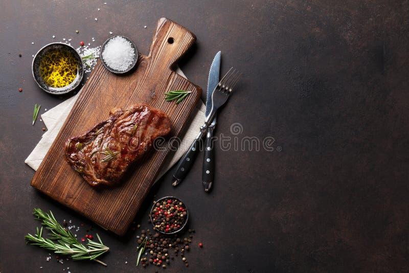 Filete, hierbas y especias asados a la parrilla de carne de vaca del ribeye imágenes de archivo libres de regalías