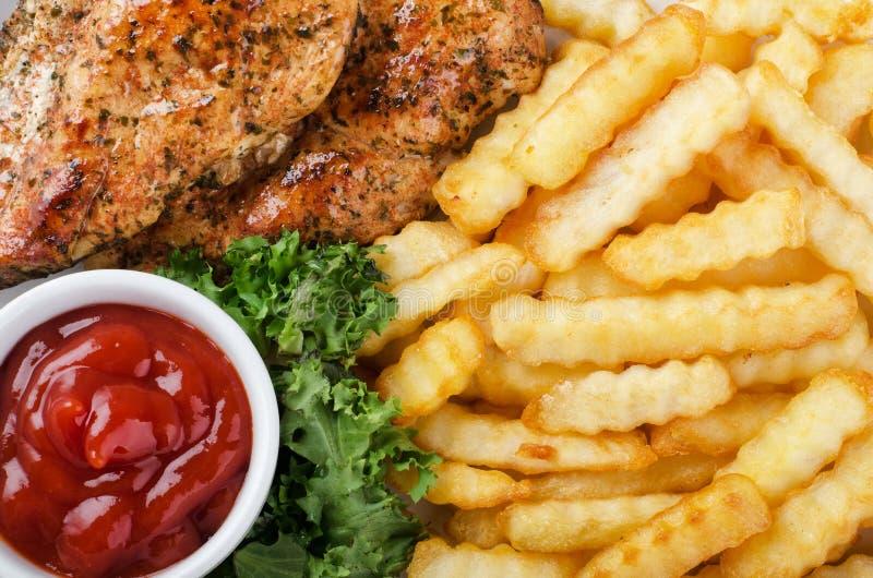 Filete, patatas fritas y ensalada asados a la parrilla del pollo fotografía de archivo