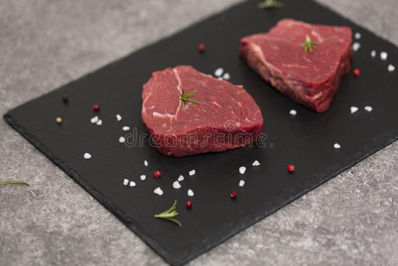 Filete y especias crudos de carne de vaca en tablero de la pizarra Carne cruda en fondo negro imágenes de archivo libres de regalías
