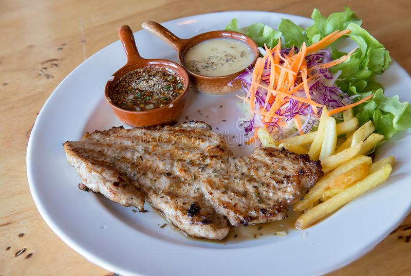 Filete y verduras asados a la parrilla del cerdo placa del cerdo asado a la parrilla con las patatas fritas y la ensalada en la t imagen de archivo