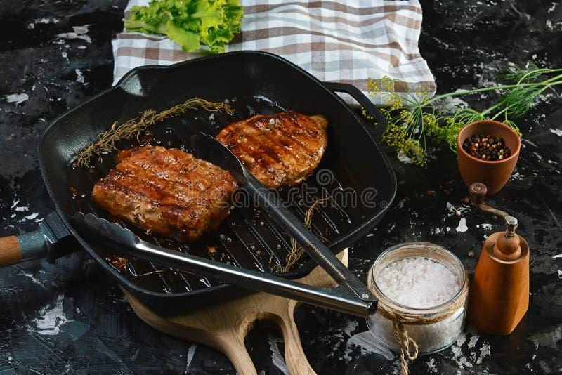 Filetes asados a la parrilla del cerdo en la parrilla con romero y especias en fondo de madera oscuro Concepto del alimento foto de archivo