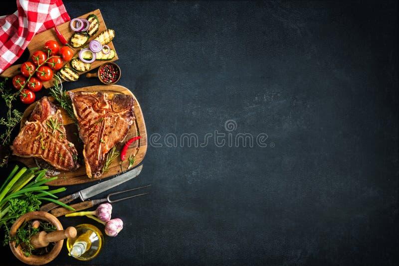 Filetes asados a la parrilla del T-hueso con las hierbas y las verduras frescas imagen de archivo libre de regalías