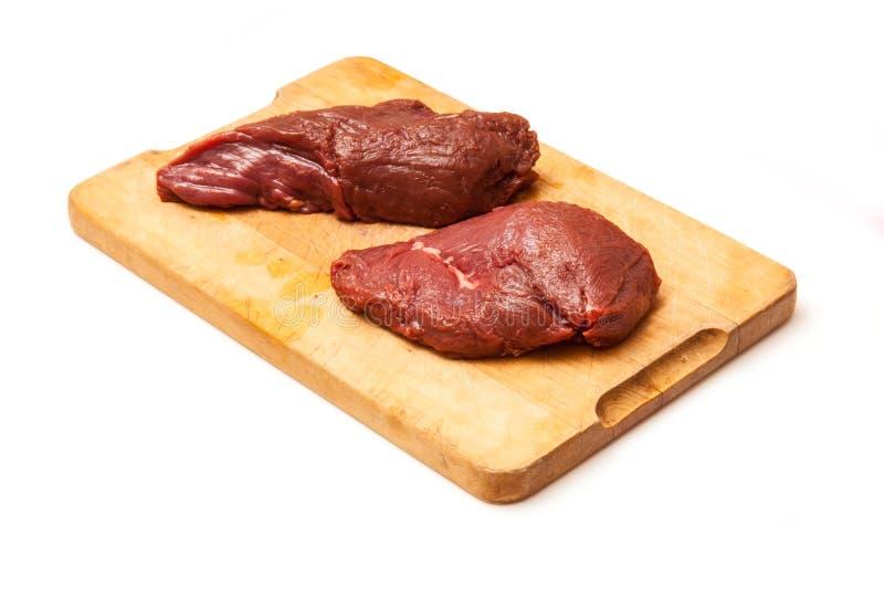 Filetes crudos de la carne del canguro en tabla de cortar foto de archivo