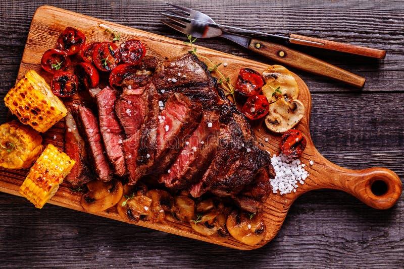 Filetes de carne de vaca con los tomates, las setas y el maíz asados a la parrilla foto de archivo